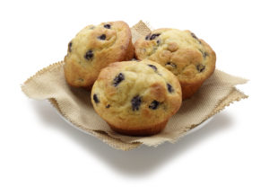 Three blueberry muffins rest on a small plate on a white background.